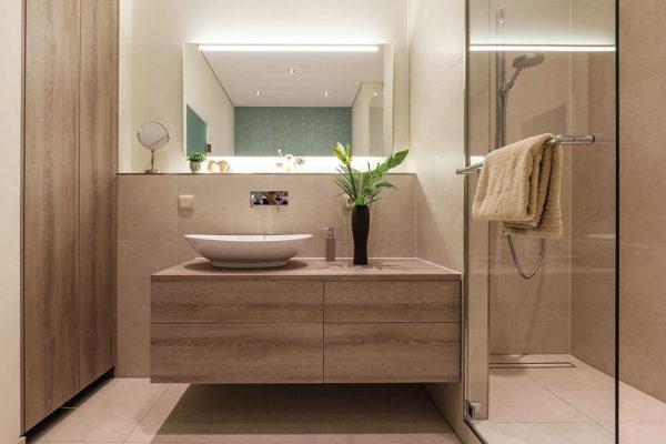 Durch den Einbau asymmetrischer Schrankelemente und einer Einbau- Waschtisch-Armatur mit einem Aufsatzbecken schufen wir ein charakterstarkes Bad.