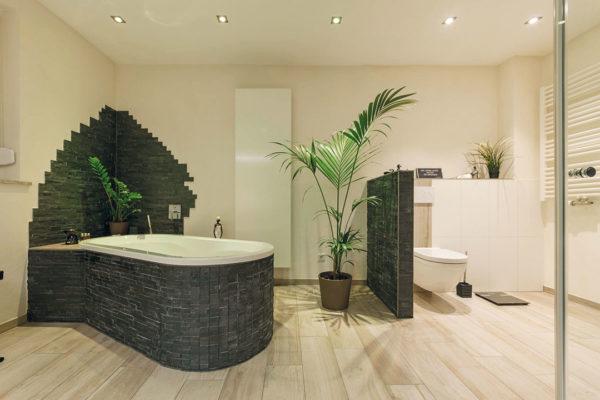 Mit einer frei stehenden Badewanne mit Akzentverkleidung, Fliesen in Holzoptik sowie einer bodengleichen Dusche schufen wir einen mediterranen Look und ein charakterstarkes Bad.