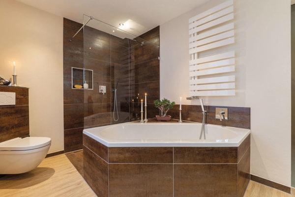 Mit einer frei stehenden Sechseckwanne sowie farblich abgesetzten Feinsteinzeugfliesen schufen wir ein charakterstarkes Bad.