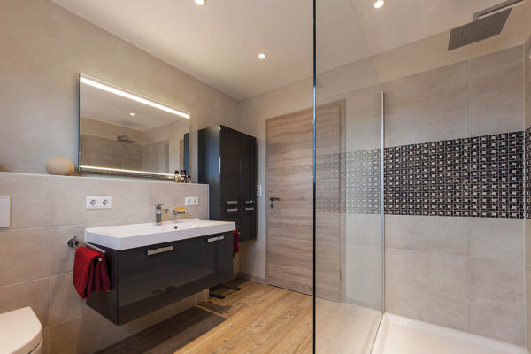 Durch Möbel mit Hochglanzeffekt und elegante Wand- und Bodenoberflächen mit farblich abgesetzten Flieseneinlagen entstand ein stilvolles und charakterstarkes Bad.
